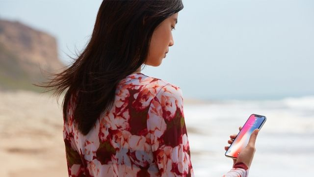 woman and iPhone X on the beach