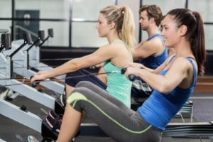 Men and women rowing in the gym