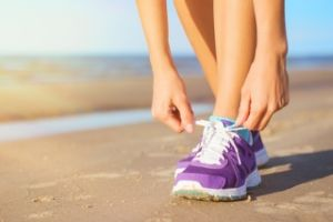 Woman lacing her purple sneakers on the beach